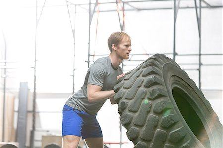 Side view of dedicated man flipping tire in crossfit gym Stock Photo - Premium Royalty-Free, Code: 693-08126930