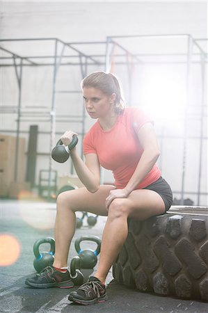 Determined woman lifting kettlebell in crossfit gym Stock Photo - Premium Royalty-Free, Code: 693-08126952