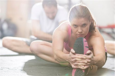 Portrait of confident woman doing stretching exercise in crossfit gym Stock Photo - Premium Royalty-Free, Code: 693-08126966