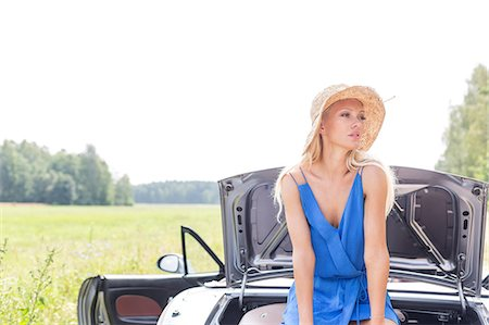 Woman looking away while sitting on convertible trunk against clear sky Stock Photo - Premium Royalty-Free, Code: 693-08127137
