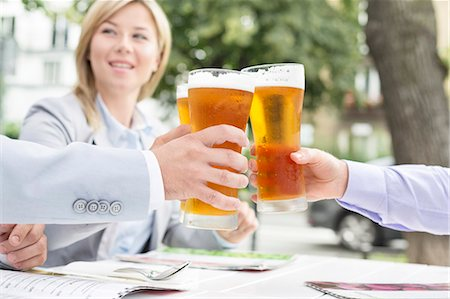 Businesspeople toasting beer glasses at outdoor restaurant Stock Photo - Premium Royalty-Free, Code: 693-08127148