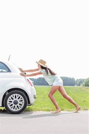 pushing - Full-length of woman pushing broken down car on country road Stock Photo - Premium Royalty-Free, Code: 693-08127141