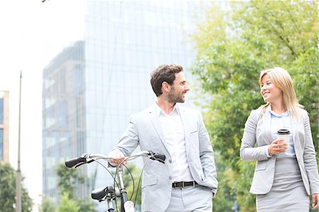 Businesspeople with bicycle and disposable cup conversing while walking outdoors Stock Photo - Premium Royalty-Free, Code: 693-08127166