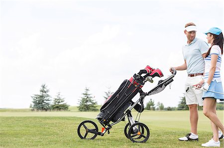 pushing - Friends with equipment talking while walking at golf course against clear sky Stock Photo - Premium Royalty-Free, Code: 693-08127234