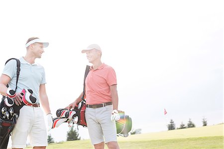 Smiling men talking at golf course against clear sky Stock Photo - Premium Royalty-Free, Code: 693-08127277