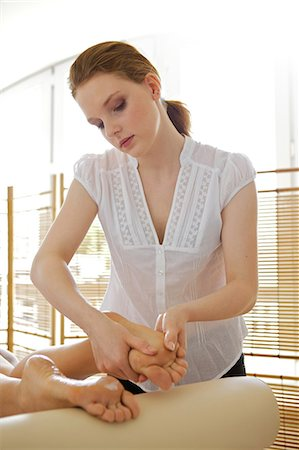 foot massage - Young woman receiving foot massage from masseuse Stock Photo - Premium Royalty-Free, Code: 693-08127479
