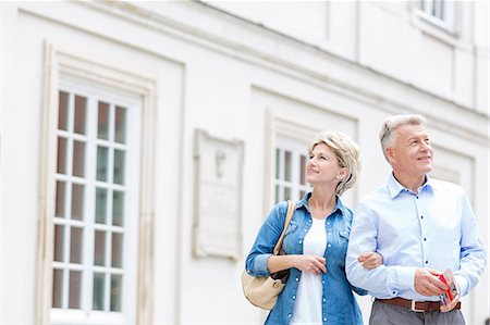 Smiling middle-aged couple standing with arm in arm outside building Stock Photo - Premium Royalty-Free, Code: 693-08127709