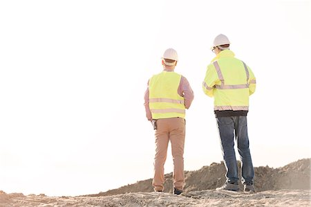 Rear view of architects standing at construction site against clear sky Stock Photo - Premium Royalty-Free, Code: 693-08127763