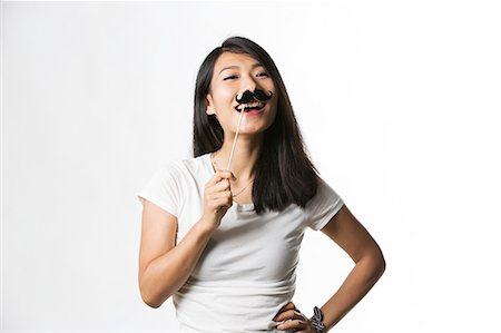 Chinese woman having fun with a fake mustache Stock Photo - Premium Royalty-Free, Code: 693-08769604