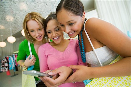 Three Girls Looking at Cell Phone picture Stock Photo - Premium Royalty-Free, Code: 693-03299497