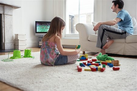 Girl (5-6) sitting on floor, playing with blocks, father watching television Stock Photo - Premium Royalty-Free, Code: 693-03305063