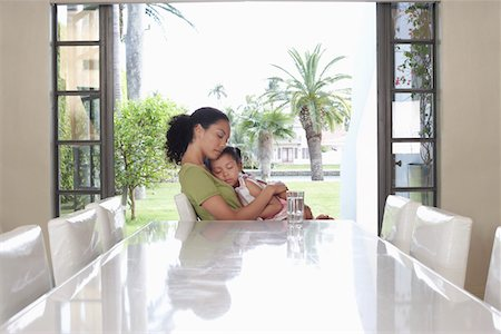 Mother and daughter (5-6 years) embracing, sitting at dining table Stock Photo - Premium Royalty-Free, Code: 693-03305703