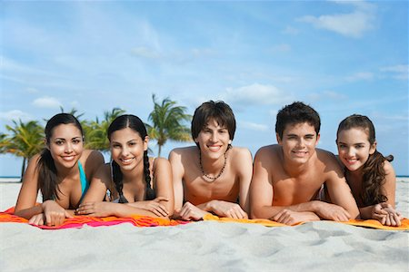 Group of teenagers (16-17) lying in row on beach towels, portrait Stock Photo - Premium Royalty-Free, Code: 693-03305814