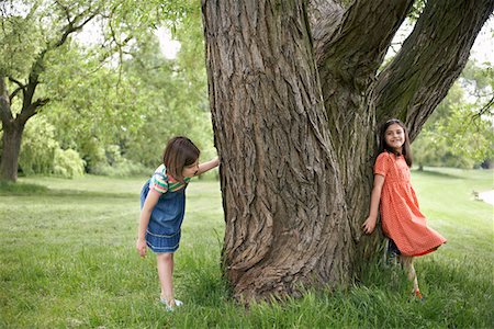 Two girls (7-9) playing hide and seek by tree Stock Photo - Premium Royalty-Free, Code: 693-03306970