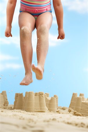 preteen girl feet - Girl (7-9 years) jumping on sand castle on beach, low section Stock Photo - Premium Royalty-Free, Code: 693-03307024