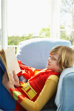 Young boy (7-9) sitting in armchair reading, wearing superhero costume, side view Stock Photo - Premium Royalty-Free, Code: 693-03307205