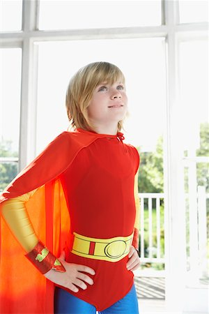 Portrait of young boy (7-9) in superhero costume, hands on hip, indoors Stock Photo - Premium Royalty-Free, Code: 693-03307202
