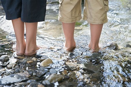 Two boys (7-9, 10-12) standing in stream, low section, back view Stock Photo - Premium Royalty-Free, Code: 693-03307988