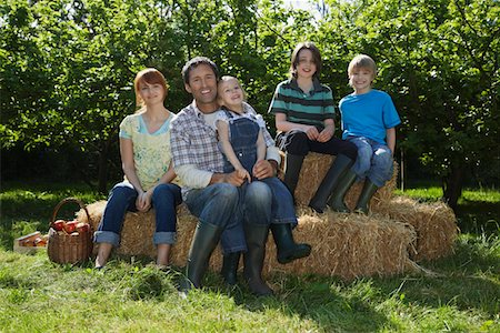 family apple orchard - Parents with three children (3-6) sitting on hay bales near orchard, portrait Stock Photo - Premium Royalty-Free, Code: 693-03308317