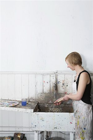 Artist cleaning paintbrush at sink in studio, side view Stock Photo - Premium Royalty-Free, Code: 693-03309432