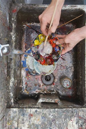Artist rinsing palette at sink in studio, view from above, close-up of hands Stock Photo - Premium Royalty-Free, Code: 693-03309443