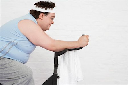 fat man exercising - Overweight man on Exercise Bike, side view Stock Photo - Premium Royalty-Free, Code: 693-03302948