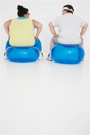 fat man exercising - Overweight man and woman Resting on Exercise Balls, back view Stock Photo - Premium Royalty-Free, Code: 693-03302950