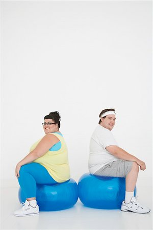 fat man exercising - Overweight man and woman sitting back to back on exercise balls, portrait Stock Photo - Premium Royalty-Free, Code: 693-03302951