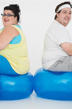 fat man exercising - Overweight man and woman sitting back to back on exercise balls, portrait Stock Photo - Premium Royalty-Free, Code: 693-03302952