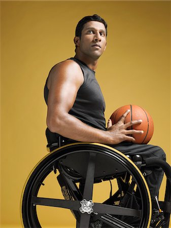 paraplegic male model - Paraplegic athlete sitting in wheelchair holding basketball, side view Stock Photo - Premium Royalty-Free, Code: 693-03302975