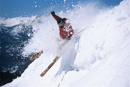 Skier skiing through powdery snow on ski Slope Stock Photo - Premium Royalty-Free, Code: 693-03303828
