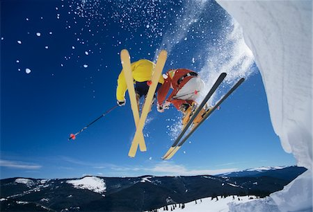 Skiers launching off snow bank, Hitting the Slopes, low angle view Stock Photo - Premium Royalty-Free, Code: 693-03303821
