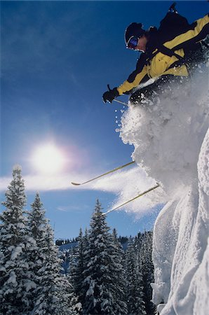 Skier skiing through snow, jumping from snow bank Stock Photo - Premium Royalty-Free, Code: 693-03303822