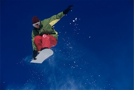 Snowboarder jumping, holding snowboard Stock Photo - Premium Royalty-Free, Code: 693-03303823