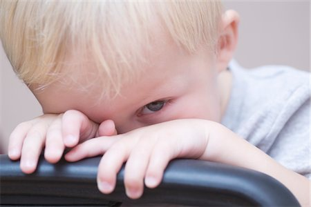 shy baby - Blonde toddler peeks over chair, looking at camera Stock Photo - Premium Royalty-Free, Code: 693-03317934