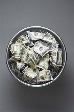 Dollar bills in wastebasket, view from above Stock Photo - Premium Royalty-Free, Code: 693-03311177