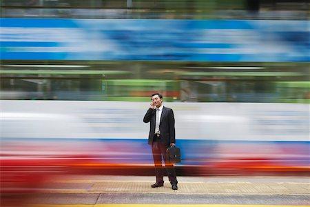 China, Hong Kong, business man using mobile phone, standing on street, long exposure Stock Photo - Premium Royalty-Free, Code: 693-03311562