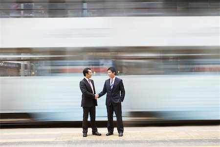 China, Hong Kong, two business man shaking hands, standing on street crossing, long exposure Stock Photo - Premium Royalty-Free, Code: 693-03311563