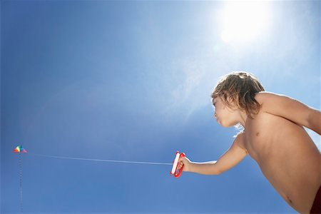 Boy (7-9) flying kite, low angle view Stock Photo - Premium Royalty-Free, Code: 693-03311854