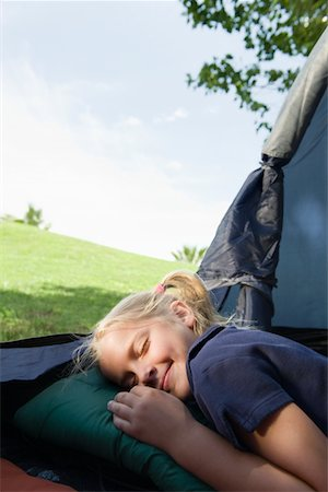 Girl pretending to sleep, with a smile in a tent Stock Photo - Premium Royalty-Free, Code: 693-03440756