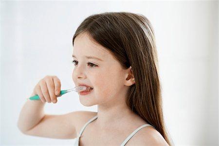 Girl Brushing Teeth in bathroom, close up Stock Photo - Premium Royalty-Free, Code: 693-03557241