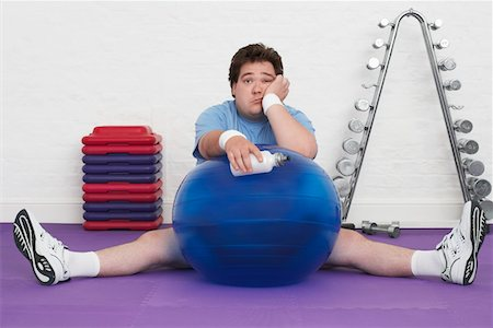 fat man balls - Overweight Man sitting on floor with exercise ball in health club, portrait Stock Photo - Premium Royalty-Free, Code: 693-03557450