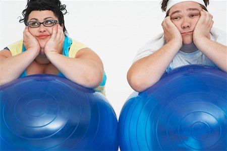 fat man exercising - Disinterested overweight man and woman lying on Exercise Balls, close up Stock Photo - Premium Royalty-Free, Code: 693-03557464