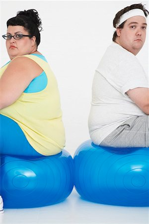 fat man exercising - Unhappy overweight man and woman sitting back to back on exercise balls, portrait Stock Photo - Premium Royalty-Free, Code: 693-03557462