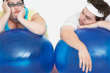 fat man exercising - Disinterested overweight man and woman lying on Exercise Balls, close up Stock Photo - Premium Royalty-Free, Code: 693-03557463