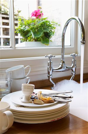 Stack of Dirty Dishes and silverware by Sink with running water below window with flower Stock Photo - Premium Royalty-Free, Code: 693-03564524