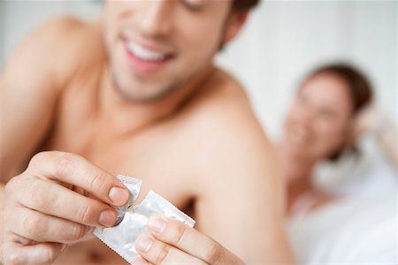 Couple in bed, man opening condom, close up of condom Stock Photo - Premium Royalty-Free, Code: 693-03564919