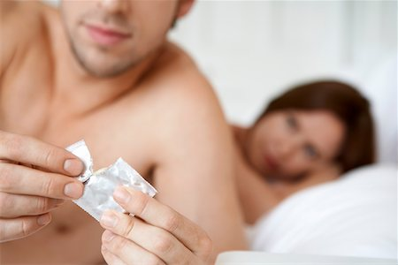 Couple in bed, man opening condom, close up of condom Stock Photo - Premium Royalty-Free, Code: 693-03564920
