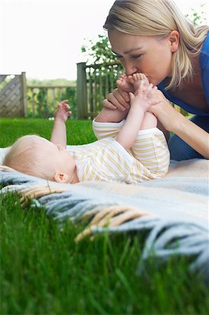 Mother and baby lying on lawn in garden Stock Photo - Premium Royalty-Free, Code: 693-03565064
