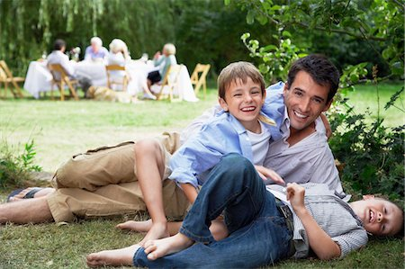 Father and two sons (7-10) having fun on grass in garden Stock Photo - Premium Royalty-Free, Code: 693-03565220